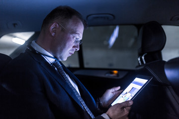 Businessman working remotely on business trip, using digital tablet, sitting in the back seat of taxi car.