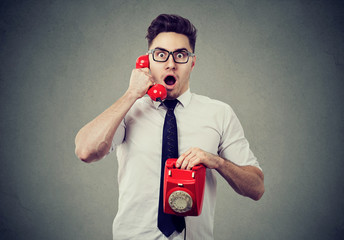 Amazed shocked man talking on a telephone