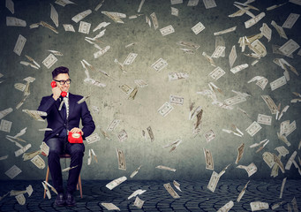Successful businessman talking on the phone under money rain