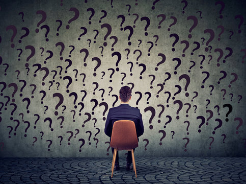 business man sitting on a chair in front of a wall has many questions, wondering what to do next