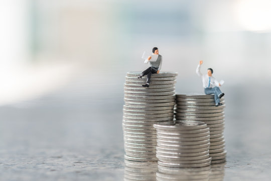 Business, Money and planning concept. Two businessman miniature figures sitting and reading a newspaper on top of stack of silver coins and face to face for talking.