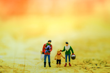 Family Travel Concept. Parent (Male and female) and child miniature figures standing on world map.