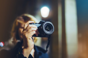 photographer girl enjoying night street in trip, traveler relax lifestyle concept, hipster hiker tourist making photo, holding in hands camera on background of evening city, blogger view in holiday