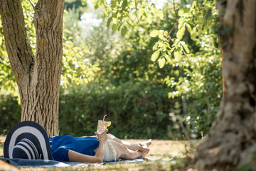 Woman lying relaxing in the shade of a tree in a  garden