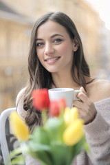 Beautiful girl having a cup of coffee in her balcony