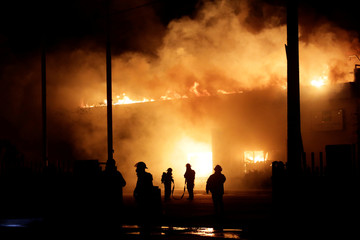Firefighters try to extinguish a fire engulfing the facilities of plastic parts maker Industrias BM de Mexico's assembly factory in Ciudad Juarez