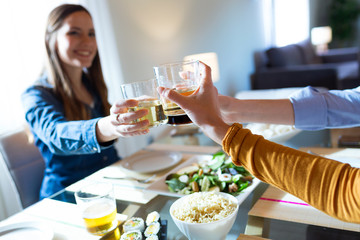 Three beautiful young woman toasting with white while eating at home.