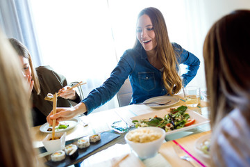 Four beautiful young women eating japanese food at home.