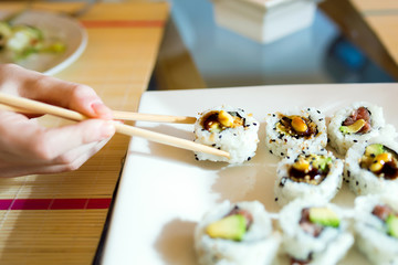 Woman's hand picking up sushi with chopsticks.