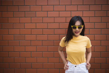 Portrait asian hipster girl on brick wall background,Thailand people wear yellow dress