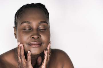Young African woman touching her face against a white background