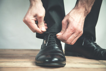 Man tying black leather shoes.