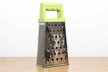 four sided cheese grater with green handle
