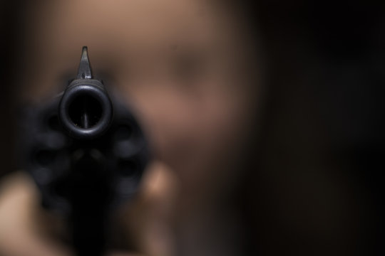 the girl is aiming from the revolver