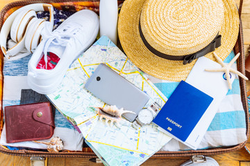woman staff in suitcase. travel concept. camera laptop wallet hat on floor. overhead view