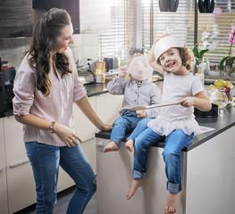 Chherful mom watching her children having fun in the kitchen