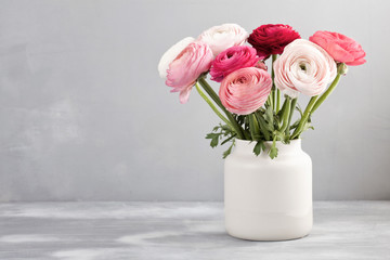 Bouquet of pink and white ranunculus flowers over the grey wall