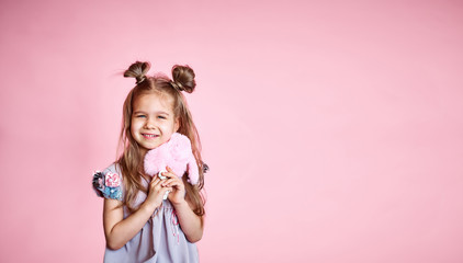happy little girl in a pink dress, with long brunette hair, on a pink background. Beautiful sweet moments of a little princess, pretty friendly child, having fun looking at the camera