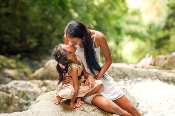 happy mother with her daughter in the tropics near the waterfall. Mothers day.