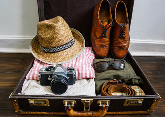 Vintage hipster clothes, shoes, hat, smartphone, accessories packed in suitcase on wooden floor. Travel concept.