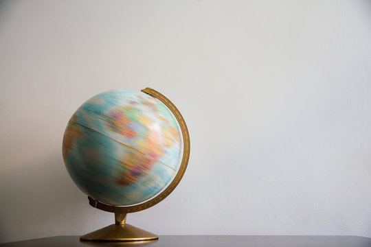 Globe model spinning on dark wooden desk. White wall empty space background.