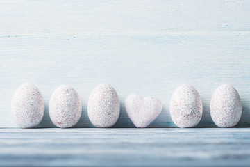 White painted Easter eggs and heart over wooden background.