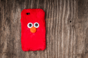 Angry bird cell phone case over rustic wood and copy space