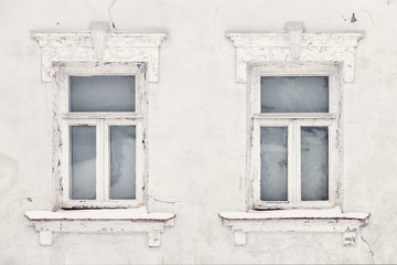 Fragment of the wall of an old house with two Windows, chipped paint and cracks