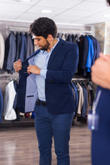 Male 25-33 years old is trying on jacket in front of the mirror