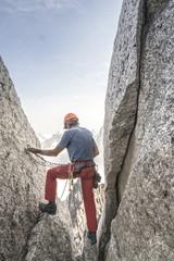 Mountain climber contemplating next rappel in Bugaboo Mountains, British Columbia, Canada