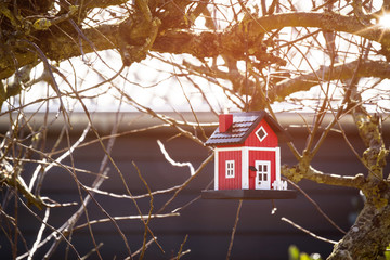 Red birdhouse barn hanging in a tree