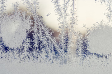 Sunrise behind a window with frost patterns