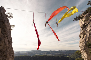 Female aerial silk gymnasts performing between two cliffs 30 meters above ground, Lower Austria, Austria
