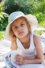 Little girl reading a book in the garden