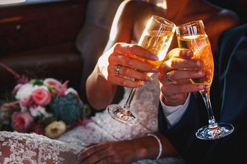Young wedding holds and climb glasses of champagne