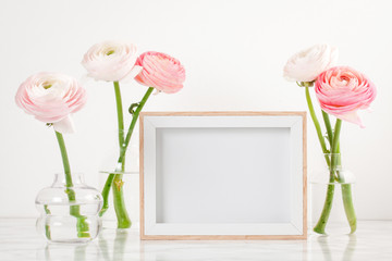 Poster frame mockup, front view, with decor elements, flowers and blank copy space over the white wall.