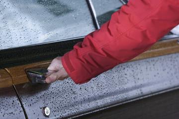 A hand opening a car door.