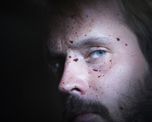 Close up of a bearded man's face splattered with blood.