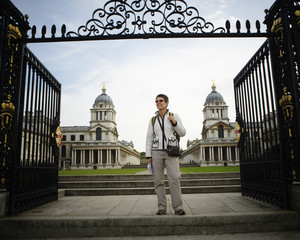 A woman stands with her guidebook in hand at the gates in front of the University of Greenwich, in Greenwich, England.