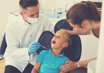 Kid with woman are visiting dentist