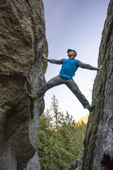 Climber bouldering between two rock faces near Elbow Lake in Fraser Valley, Harrison Mills, British Columbia, Canada