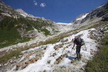 Mountaineer crossing Ashlu Creek on way to Ashlu Mountain in Coast Mountain Range, Squamish, British Columbia, Canada