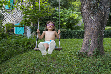Front view of girl swinging in garden in summer, Genolier, Switzerland