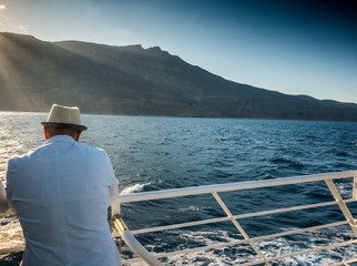 Men admiring seascape and mountain from boat, Crete, Greece