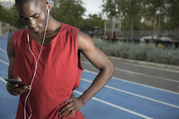 Male athlete standing on all-weather running track and listening to music on smart phone, Barcelona, Spain