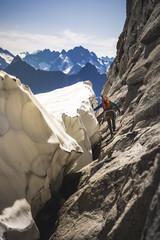 Mountain climber walking around glacier bergschrund at base of Mount Torment, North Cascades National Park, Washington State, USA