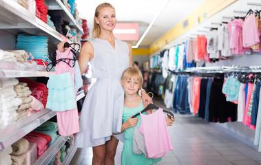 Portrait of mom with girl choosing dress