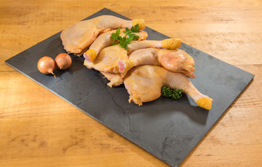 chicken legs presented on a slate on a wooden background
