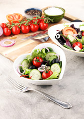 bowl of salad with vegetables and greens, with tomato, cucumber and onions.