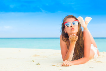 young longhaired girl in bikini and sunglasses tanning at tropical beach